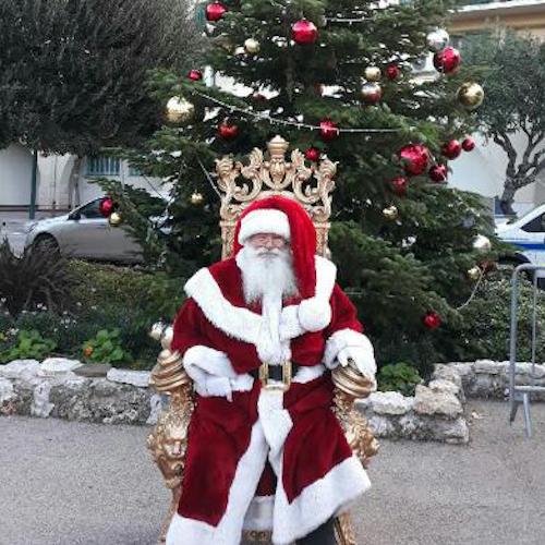 Un père Noël assis sur un trône devant un sapin