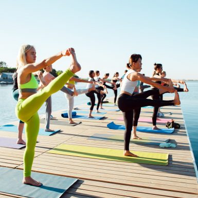 Groupe de Femmes faisant du yoga sur une jetée