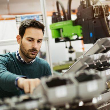 un homme tape sur une machine industrielle