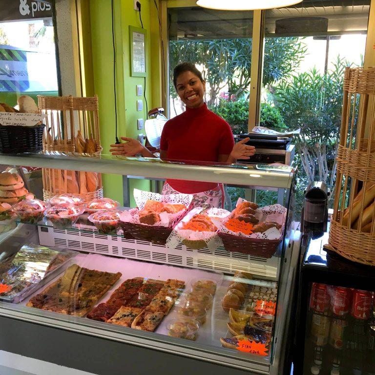 Vendeuse de l'épicerie Happy Belle devant son stand