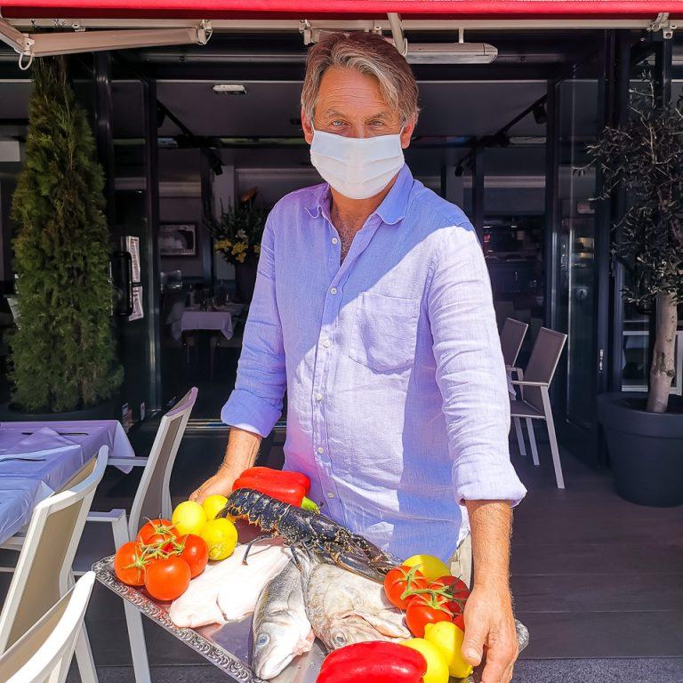 Un home tient un plateau de poisson
